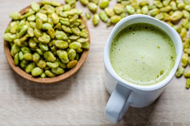Jadalne ziarna hiacyntowej fasoli przekąski i zielonej herbaty latte na drewnie