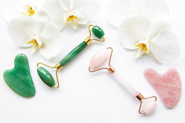 Jadeitowe rolki i kwiaty orchidei na białej powierzchni