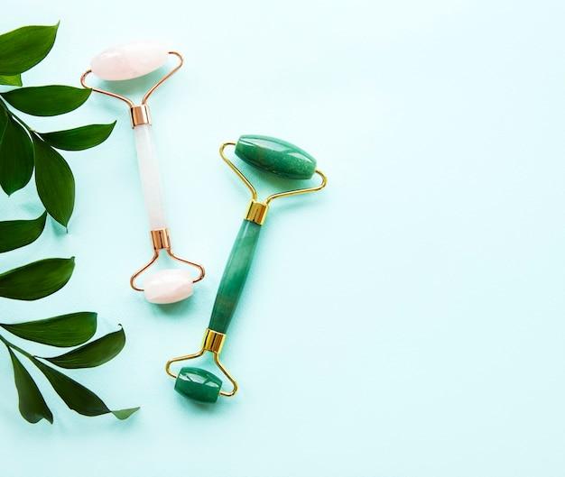 Jadeitowy wałek do masażu twarzy na pastelowym zielonym stole