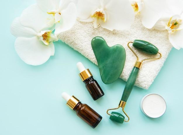 Jadeitowy wałek do masażu twarzy z kosmetykiem na pastelowym zielonym tle