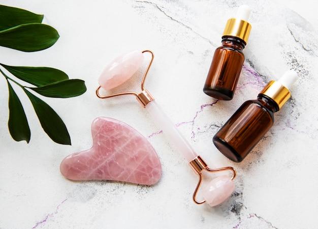 Jadeitowy wałek do masażu twarzy z kosmetykiem na tle białego marmuru