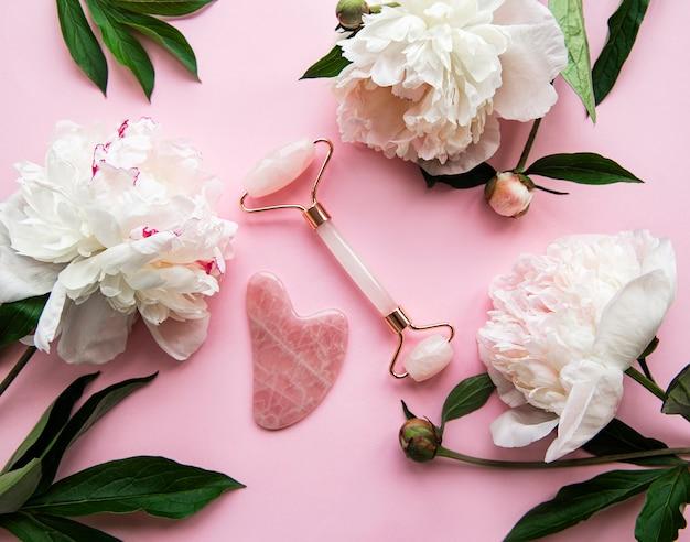 Jadeitowy wałek do twarzy do masażu twarzy, olejków do masażu i różowych piwonii.