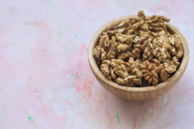 Jądra orzechów włoskich obrane orzechy w drewnianej misce na różowym tle