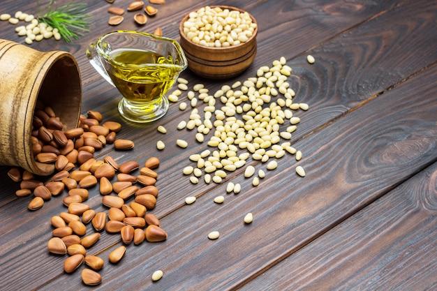 Jądra orzeszków piniowych w drewnianym pudełku i na stole. orzeszki piniowe w łupinach. olej cedrowy.