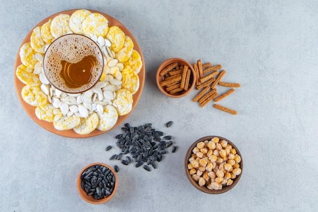 Jądro, frytki i szklanka do piwa na talerzu obok grzanki, ciecierzycy i nasion, na marmurowej powierzchni.