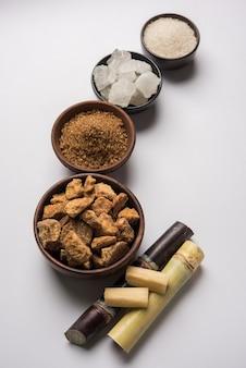 Jaggery, sugar variety i sugarcane - produkty uboczne sugar cane czy ganna umieszczone na nastrojowym tle. selektywne skupienie