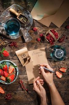 Jagoda martwa natura. jagody, herbata, długopis, kalendarz, notatnik na starym brązowym drewnianym stole, widok z góry