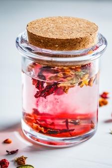 Jagodowa różowa herbata z ziele w szklanym słoju, biały tło. zawartość zdrowych napojów.