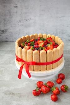 Jagodowe ciasto ozdobione dużymi truskawkami, malinami i jagodami
