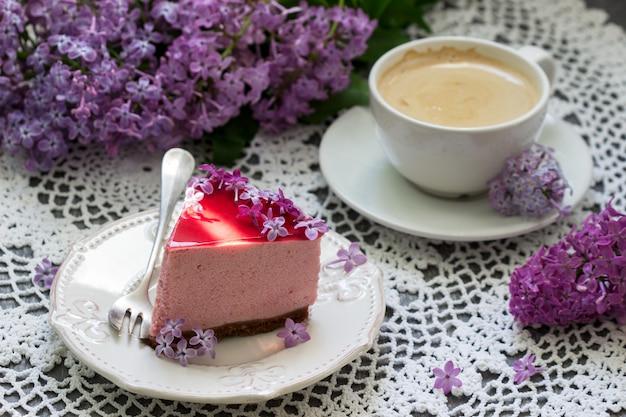 Jagodowe ciasto z musem na bazie czekolady i soku galaretkowego, ozdobione kwiatami bzu, podawane z kawą.