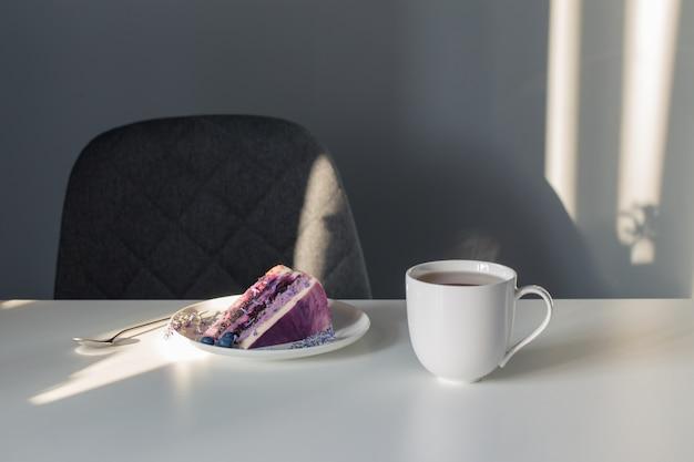 Jagodowo-lawendowy sernik na talerzu i filiżanka herbaty na białym stole
