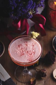Jagodowy czerwony kwaśny koktajl wśród ciemnych suszonych kwiatów w restauracji czarownicy