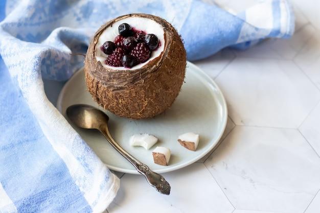 Jagodowy deser z jogurtem w filiżance kokos na lekkim tle. jeżyny, maliny, jagody, czarne porzeczki. niebieska serwetka