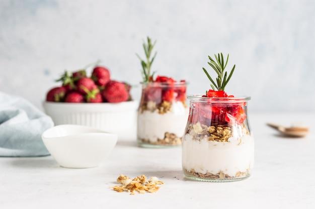 Jagodowy jogurt z jogurtem greckim, świeżymi truskawkami i muesli w słoikach. parfait zdrowe śniadanie w szklanym kubku