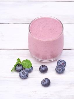 Jagodowy jogurtu szkło na białym drewnianym stole