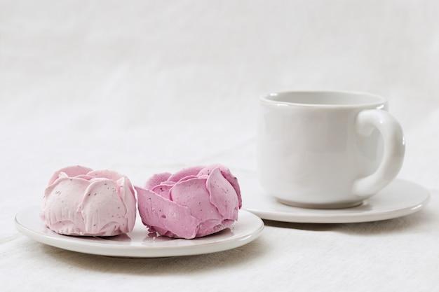 Jagodowy marshmallow kwitnie tulipany na bielu talerzu z filiżanką herbata. pięknie zdobiony deser. piękny i pyszny deser niskokaloryczny. jagodowy zefir na lekkim tle z kopii przestrzenią dla teksta.