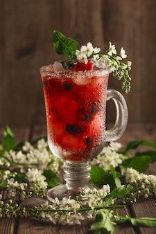 Jagodowy napój bezalkoholowy z lodem na drewnianej powierzchni z kwiatami