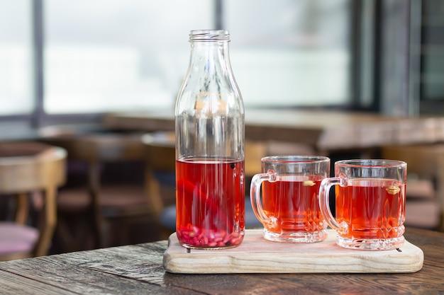 Jagodowy napój kombucha i szklane kubki na drewnianym stole. zdrowy napój fermentowany z probiotykami