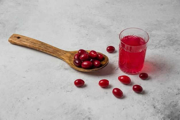 Jagody cornel w drewnianej łyżce i soku w szklance.