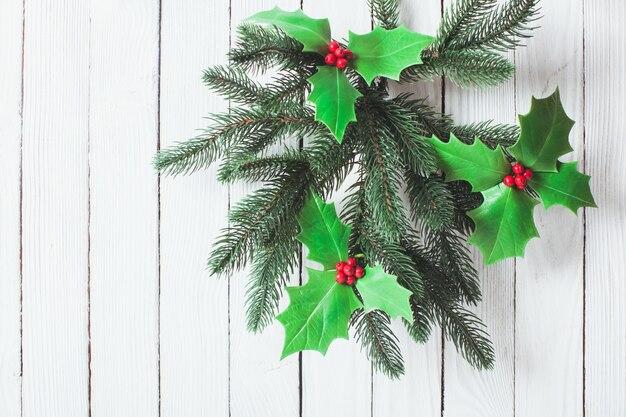 Jagody cristmas holly i gałązki jodły na białej ścianie