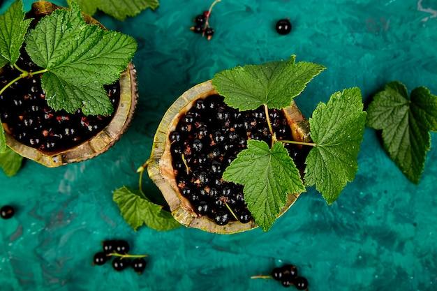Jagody czarnej porzeczki z liśćmi, czarna porzeczka w zielonych miseczkach.