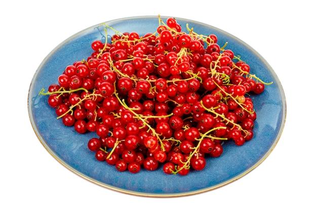Jagody. czerwone porzeczki na niebieskim talerzu. menu wegetariańskie. studio photo