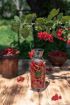 Jagody czerwonej porzeczki w szklanej butelce i miski na drewnianym stole w ogrodzie, słoneczny dzień, z bliska.