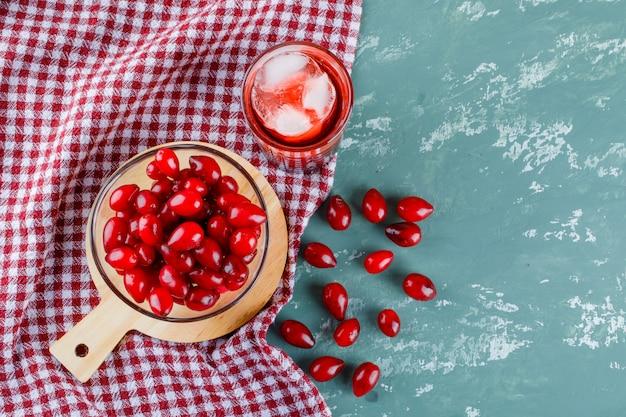 Jagody dereń w misce z napojem, deska do krojenia na tynku i szmatka piknikowa