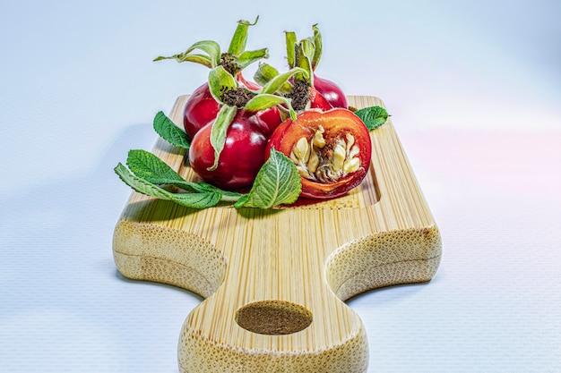 Jagody dzikiej róży na drewnianej bambusowej desce. naturalne naturalne witaminy. składniki na herbatę. medycyna i zdrowie.