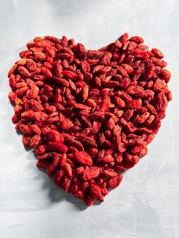 Jagody goji ułożone w kształcie serca na jasnoszarym tle.