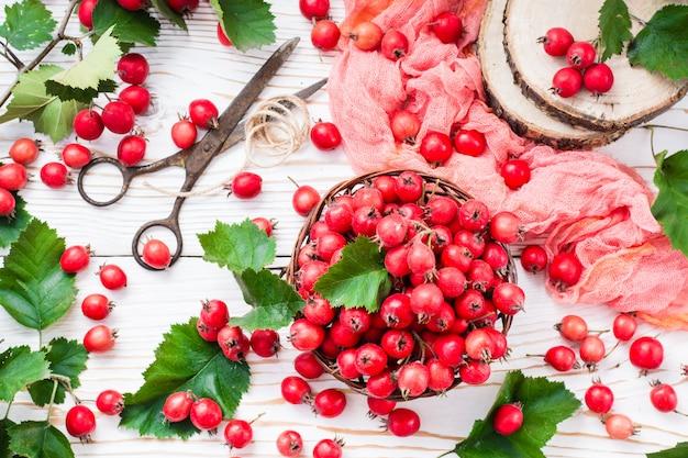 Jagody i liście głogu w łozinowym koszu na drewnianym stole, odgórny widok