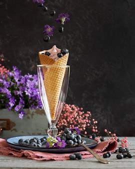 Jagody jagodowe w gofrze puchar otoczony fioletowymi kwiatami i jagodami. letni motyw. lewitacja