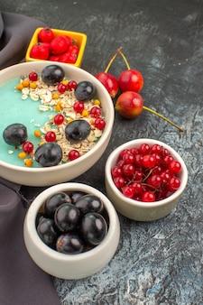 Jagody kolorowe jagody w miseczkach płatki owsiane na obrusie