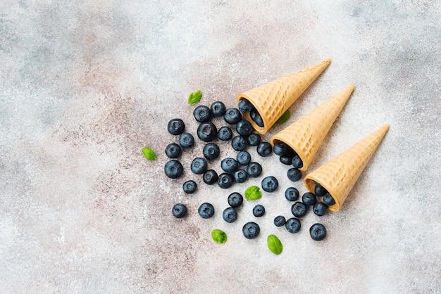 Jagody leżą w rożku waflowym i rozrzucone na betonowym stole. letni produkt sezonowy. zdrowy wegetariański deser. widok z góry