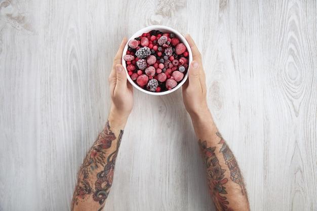 Jagody mrożone, czarna porzeczka, czerwona porzeczka, malina, borówka. widok z góry w rocznika ceramicznej białej misce na rustykalnym drewnianym stole na białym tle.