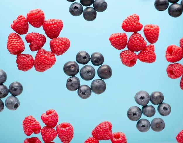 Jagody na niebieskim stole. latająca malina i jagody