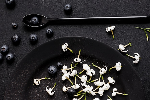 Jagody płasko leżały na ciemnym talerzu z kwiatami