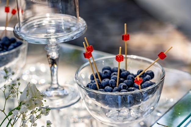 Jagody stoją w szklanym talerzu. tło z nowocześnie zaprojektowanym szklanym stojakiem.