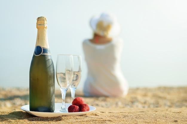 Jagody świeże truskawki, butelka szampana, szklanki i kobieta na plaży.