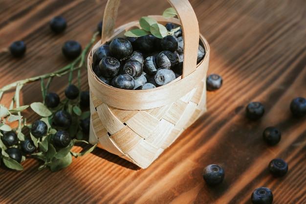Jagody w koszyczku z kory brzozy na tle drewnianych. zbiory jagód, witamin i korzyści zdrowotnych.