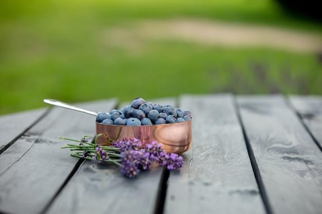 Jagody w metalowej doniczce i kwiaty lawendy wokół na drewnianym stole w ogrodzie