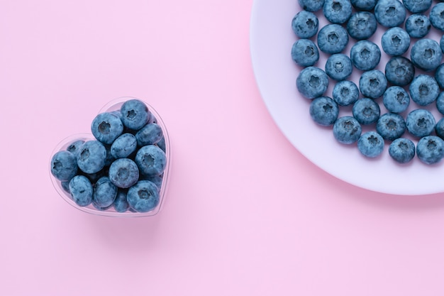 Jagody w misce w kształcie serca, jagoda na różowym talerzu, danie. abstrakcyjne tła, jasne letnie tapety. selektywna ostrość.