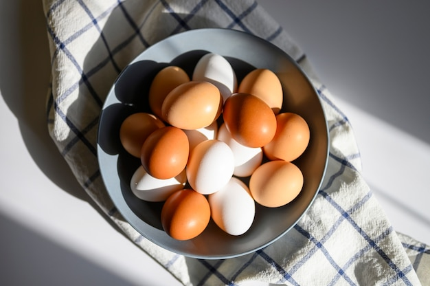 Jaja kurze biało-brązowy kolor w szarym talerzu na sprawdzonym ręczniku kuchennym na białym stole. koncepcyjne produkty rolne i naturalne odżywianie. ostre światło słoneczne i cienie