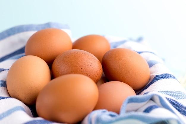 Jaja kurze brązowe z rustykalną szmatką na jasnoniebieskim tle.