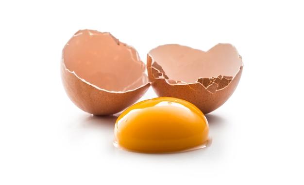 Jaja kurze i rozbite jajko z żółtkiem na białym tle.