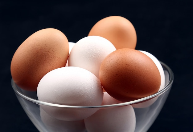 Jaja kurze leżą na talerzu w ciemności