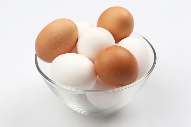 Jaja kurze leżą w talerzu na białym tle