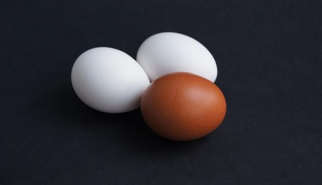 Jaja kurze lub indyka o różnych kolorach brązowym i białym na czarnym tle zbliżenie trzech jaj i widok z góry