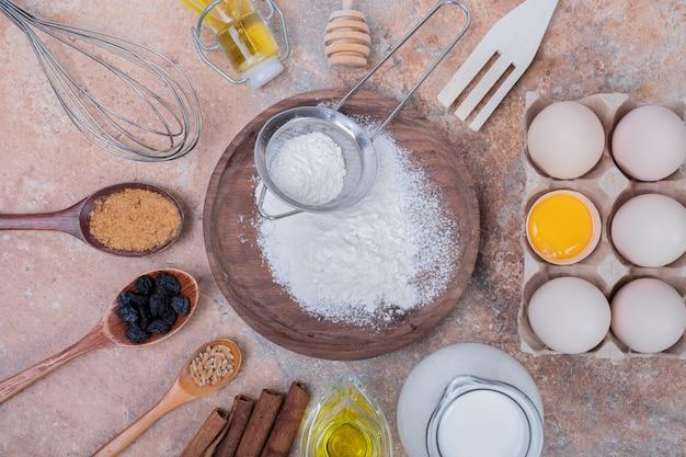 Jaja kurze, mleko, mąka i przyprawy na marmurowej powierzchni.
