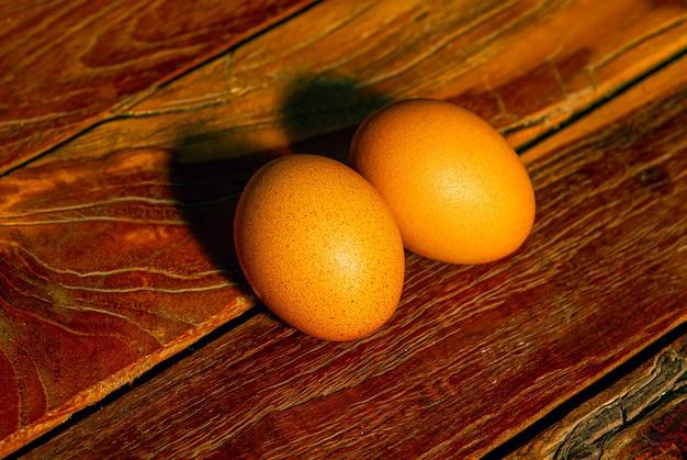 Jaja kurze na starym stole z drewna tekowego, płytko skupione